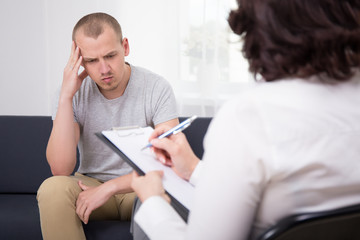 sad man listening to employer on interview