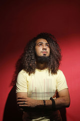 Man fashion and long beautiful curly hair against red background