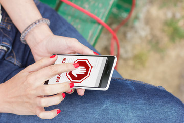 Young woman using mobile smartphone outdoors with ad blocker on