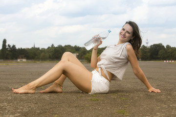 young woman sitting on pavement and drinking water