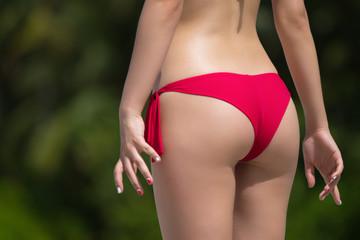 Beautiful female buttocks in bikini from the back. Sexy woman  o