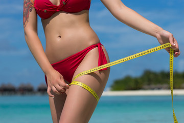 Sexy woman at the beach in bikini with measure tape. The concept