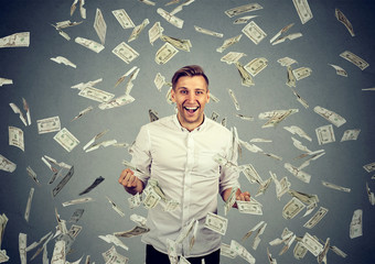 man celebrates success under money rain falling down dollar bills
