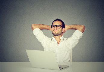 Smiling dreaming man in glasses looking up while working at laptop