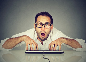 Crazy nerdy looking man in glasses typing on keyboard
