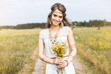 Close-up portrait of a beautiful young sweet gentle hippie girl in a white dress, holding a bouquet of wildflowers, walking outdoors, flash tattoo, indie, Bohemia, boho style, fashion accessories
