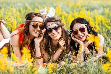 Three cute hippie girl lying on the grass among the wildflowers, best friends having fun and laughing,  sunglasses, feathers in their hair, bracelets, flash tattoo, indie, Bohemia, boho style