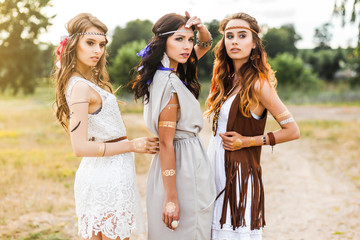 Three cute beautiful hippie girl walking along the road, outdoors, best friends are traveling, make-up, long hair, feathers in their hair, bracelets, flash tattoo, indie, Bohemia, boho style