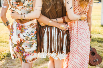 Three cute beautiful hippie girl in the setting sun, outdoors, the best of friends hugging and having fun, long hair, feathers in their hair, bracelets, flash tattoo, indie, Bohemia, boho style
