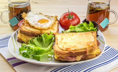 French breakfast for two people - Tasty breakfast for two persons with specific french food, croque madame (with egg) and croque monsieur, seasoned with fresh salad and tea.