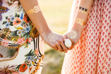 Two cute hippie girl in the setting sun, outdoors, holding hands, best friends, feathers in long hair, bracelets, flash tattoo, indie, Bohemia, boho style dresses, trendy accessories