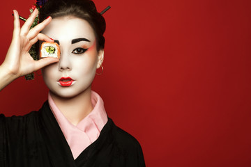 Portrait of young heisha in kimono holding a piece of sushi in front of her eye on red background.  Studio shot. Copy space