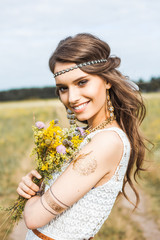 Pretty amazing gentle young hippie girl on the nature in the open air, the feathers in her hair, white dress, leather and gold accessories, flash tattoo, indie, Bohemia, boho style, fashion, flowers