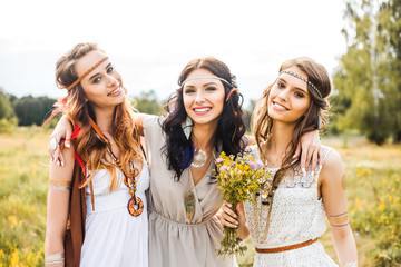 Summer holidays, travel and people concept -Three beautiful cheerful hippie girls, best friends, trendy hairstyles, feathers in her hair, white dress, tattoo flash, accessories, Bohemian, Boho Style