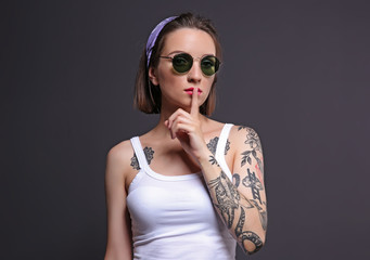 Beautiful young woman with tattoo wearing sunglasses and posing on gray background