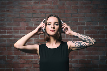 Beautiful young woman with tattoo wearing headphones and posing on brick wall background
