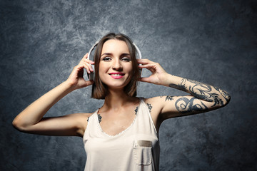 Beautiful young woman with tattoo wearing headphones and posing on gray background