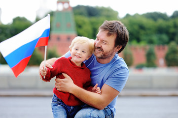 Family with russian flag with Moscow Kremlin on background