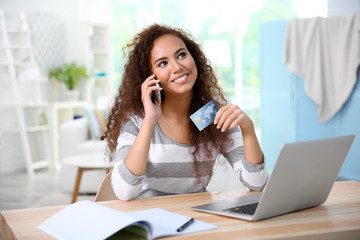 Beautiful young woman using credit card and phone for online shopping