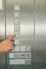 Female's Hand Pressing First Floor Button In Elevator