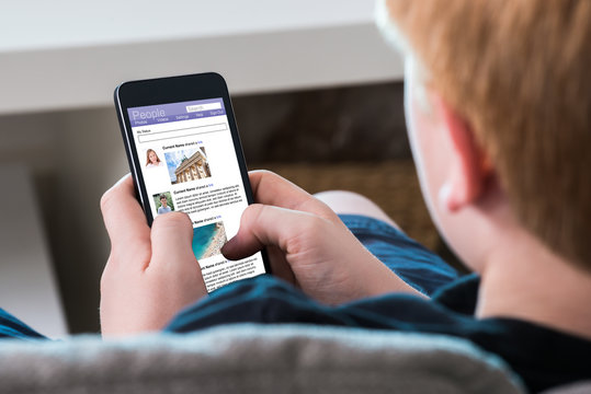 Boy Using Social Networking Site On Mobile Phone