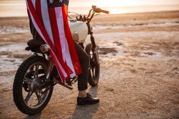 Cropped image of a man wearing american cape on motocycle