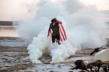 Brutal man wearing usa flag cape posing in white smoke