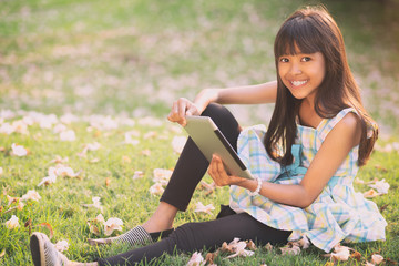 Happy asian girl sitting on grass with tablet computer looking at camera