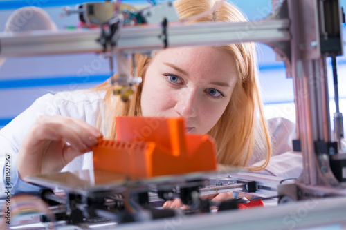 Wall mural Young woman work with 3d printer