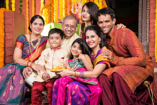 Indian family celebrating ganesh festival or diwali, eating sweets, taking selfie and other activities