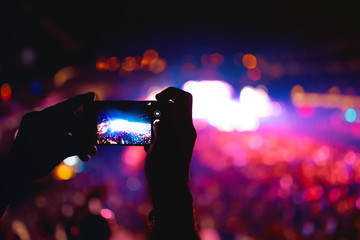 Silhouette of hands using camera phone to take pictures and videos at music concert, festival. Soft effect on photo