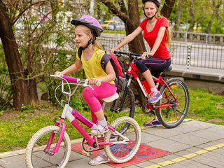 Bikes bicyclist girl. Two sisters girls wearing bicycle helmet with rucksack ciclyng bicycle. Girls cycling on yellow bike lane. Bike share program save money and time at city street. Summer outdoor.