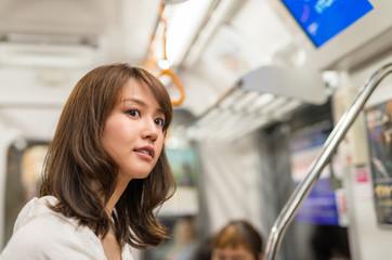 Asian girl standing inside city subway train