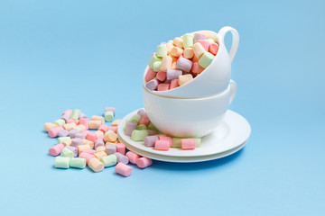 Pastel marshmallow in a white cup on a blue background. Sweet unhealthy food. Minimalism style