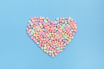 Pastel marshmallow in the shape of a heart on a blue background overhead shot