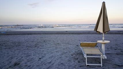 umbrellas and chairs in riccione rimini beach at sunset