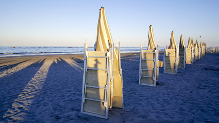 umbrellas and chairs in riccione rimini beach at sunset