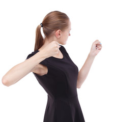 skinny woman funny fights waving his arms and legs. Isolated over white background. Blonde in a short black swung to strike.