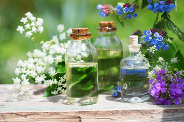 Essential aroma oil  in bottles on wooden background outdoor.