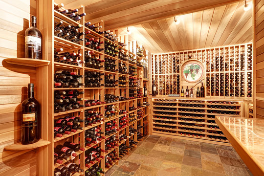 Bright home wine cellar with wooden storage units with bottles.