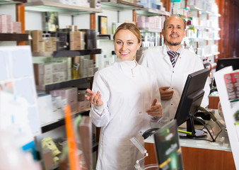 Two adult pharmacists standing next to shelves