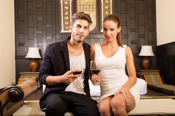 A young and happy couple enjoying a glass of wine in a asian style hotel room on their vacations..