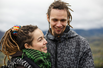 Couple with dreadlocks smiles while standing outside in misty we
