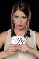 beautiful serious woman holds in her hands a winning combination of cards