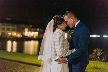 Romantic wedding portrait. Happy newlywed groom going to kiss his new wife. Night lake illuminated with bright light from banquet hall windows at background