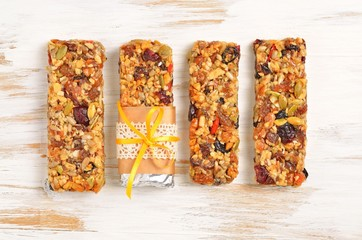 Homemade gluten free granola bars on white wooden background. Top view.