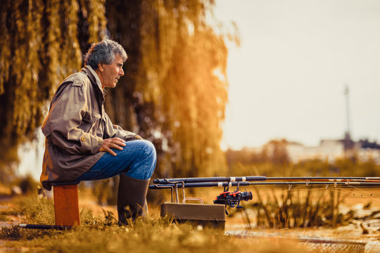 Senior man fishing on a freshwater lake sitting patiently