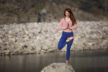 Amazing beautiful girl does yoga near the river.