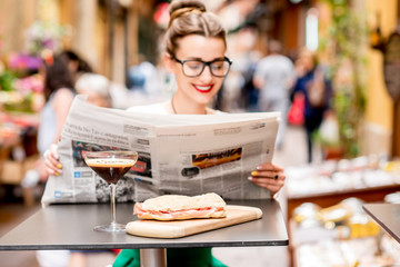 Young woman reading newspaper with shakerato drink and panini on the table outdoors on the street in italian city. Traditional italian lunch. Image with small depth of field, focused on the food