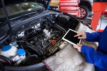 Mechanic using a digital tablet while servicing car engine